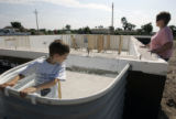 Jarett Rushton and his mother Jana check out the progress of their new home being built in Holly,...