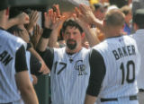Colorado Rockies first baseman Todd Helton gets swarmed by high-fives in as he scores in the...