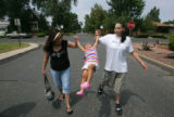 Neighbor and friend Bernadette Mercado (cq), left, swings her daughter Alysa DeHerrera (cq), 2,...
