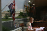 MJM087 With her American flag flying upside down in protest to the war in Iraq (seen reflected in...