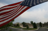 Beth Hammer (cq) flies her American flag flying upside down in protest to the war in Iraq outside...