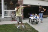 Vince Sanchez, 10 sitting on the porch in background watches his brother Evan, 8, try to balance...