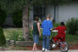 Neighborhood kids, (from left) Alex Biasizzo, 12, Dylin Mandel, 12 and Randy Canister, 12, look at...