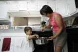 Duran Walters (cq), a native of Mongolia, shows her son Adrian, 2, how to place buuz, or...