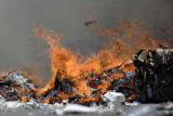 Recycled paper bales burn as firefighters work to contain a two-alarm fire at Waste Management,...