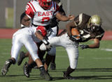 Thomas Jefferson running back Ryan Allen, right, breaks a tackle from Denver East defenders Josh...