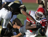 Denver East's Quentin Hildreth, right, slips past Thomas Jefferson defender Brandon Lowe, left, in...