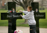 (Centennial, Colo., April 14, 2005) Tyler Strole (cq), 13, lays a rose on the cross memorializing...