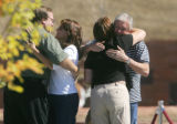 John Tomlin, left, father of Columbine shooting victim John Tomlin, embraces an unidentified woman...