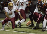 Faith Christian quarterback Steve Carbajal, left, fumbles the ball in the third quarter of play as...