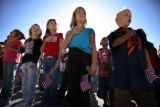 Holding small American flags students- first graders who were babies in 2001 - the 9/11 disaster,...