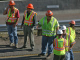CDOT workers gather near the scene where a fellow road worker who was taking down a barricade on...