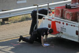 Colorado State Patrol accident reconstruction team examines the scene where a road worker who was...