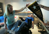 Tracy Keil (cq) hands off an Army banner signed by her husband Staff Sgt. Matt Keil (cq) as they...