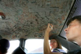(from left) Greg Harbour (cq) adds a message to the ceiling of his friend's car, as Justin Greer...