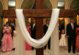 Fathers and daughters stand behind a cross as they wait to place white roses at the foot of the...