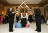 Randy Wilson and kevin Moore, right, hold swords as a father and his two daughters lay roses at...