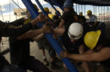 (DENVER, Colo., May 27, 2004) All the workers moved from pole to pole pushing and sweating getting...