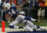 Dallas Clark scores a touchdown as he is dragged out of bounds by Ian Gold in the third quarter of...