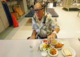 David Simons (cq), 66, of Fort Collins, puts pepper on his dinner as he wears a halo vest at the...