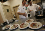 Chef Rocky Durham (cq) and chef Noe Cano (cq) plate up their enchiladas, posole and green chili...