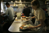 Waitress Gayle Lampert (cq) picks up an order to serve to customers while Ronal Garcia (cq), left,...