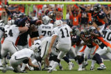 [JOE1704] Denver Broncos defenders try to block Oakland Raiders kicker Sebastian Janikowski's...