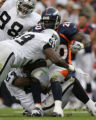 [JOE1981] Denver Broncos Travis Henry, #20, takes a hit by Oakland Raiders Warren Sapp, #99, in...