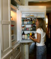 Deborah Baker (cq) looks for something in her refrigerator in her kitchen at her home on Ash...