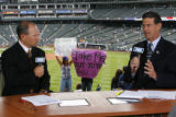 DM2589  Fans hold up signs as Drew Goodman, left, and George Frazier broadcast their pregame...