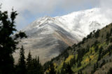 Foliage and trees burst into color and snow dusts the Colorado Rockies seen from the  road leading...