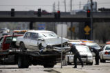 A worker loads a car onto a wrecker Monday at the intersection of 45th and Havana after it was...