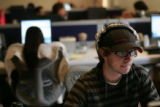 Matt Ferry  (cq), left, content delivery assistant, works at his computer in the offices of...