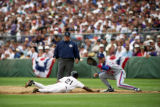 Colorado Rockies Eric Young slides back to first base to avoid the tag of Montreal Expos Archi...