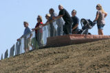 People look down on the memorial from rebel Hill as family members tour the Columbine Memorial...