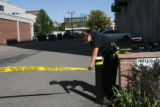 An unidentified DPD police officer installs police tape at the entrance to the crime scene. The...