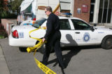An unidentified DPD officer pulls back police tape for another officers vehicle to enter the crime...