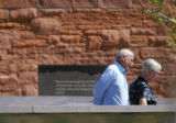 Two unidentified persons look at the memorial as family members tour the Columbine Memorial before...