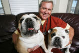 TV newsman Ernie Bjorkman hugs his two bulldogs, Fannie, left, and Ziggy (check spelling with...