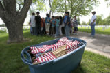 A bucket of American flags waits for the 5th grade class of Taylor Academy, Friday morning, May...