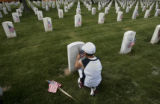 Devon DeHerrera (cq), 10, places American flags at graves, Friday morning, May 23, 2008, Fort...