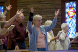 DM0130  Lavay Weinnester fights back tears as she raises her hands in praise at Bethel Lutheran...