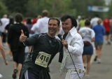 Paul Torrez (cq), Elvis, has a runner join him while he entertains  on Folsom Rd, Monday morning,...