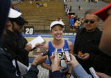 DM2677  Deena Kastor, center, of Mammoth, Cal., smiles as she talks with reporters after finishing...