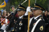 Members of the honor guard retrieve their colors at the end of a memorial service held at the...