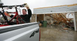 Dave Peterson loads a bike into a pick-up from the home of a  Shawn Leschinskyas they salvage what...