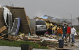 Residents and volunteers look over a home mostly leveled by the storm in Windsor, Colo. on Monday...