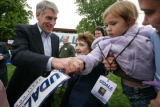 Congressman Mark Udall shakes  hands with Madeleine Whitney, 2 held by her mom, Amy Mason of...