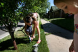 (PG13459)  Stephanie Nussbaumer takes off her son Lucas's wet shoe while helping him and his...