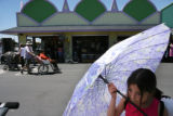 MJM081  Nayeli Dimas, 8, holds an umbrella to shade her from the sun as she waits for her family...